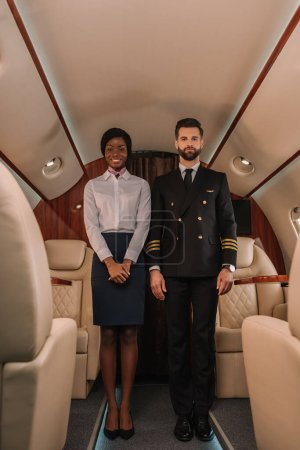 Photo pour Beau pilote confiant et souriant hôtesse afro-américaine regardant la caméra dans un avion privé - image libre de droit