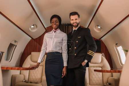 Photo pour Beau pilote positif debout avec la main dans la poche près d'hôtesse afro-américaine souriante en jet privé - image libre de droit