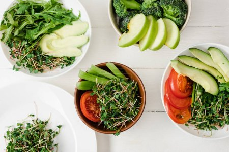 Photo pour Vue de dessus des légumes et fruits frais avec microgreen dans des bols sur la surface en bois blanc - image libre de droit