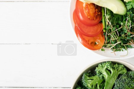 Photo for Top view of fresh microgreen, tomato, avocado and broccoli in bowls on white wooden surface - Royalty Free Image