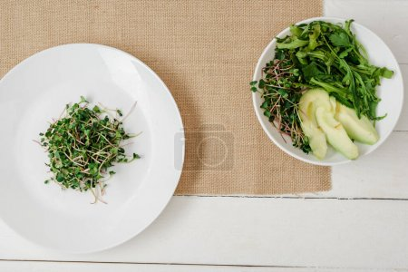 Photo for Top view of fresh microgreen on plate near bowl of green salad on beige napkin on white wooden surface - Royalty Free Image