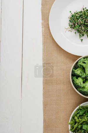Photo for Top view of fresh microgreen on plate near bowls of green vegetables on beige napkin on white wooden surface - Royalty Free Image