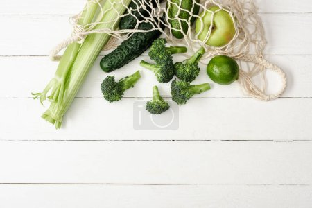 Photo for Top view of fresh green fruits and vegetables in string bag on white wooden surface - Royalty Free Image