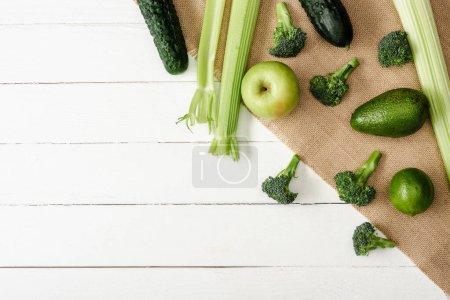 Photo pour Vue de dessus des fruits et légumes verts frais sur le sac sur la surface en bois blanc - image libre de droit