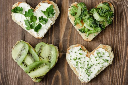 Photo for Top view of heart shaped canape with creamy cheese, broccoli, microgreen, parsley and kiwi on wooden surface - Royalty Free Image