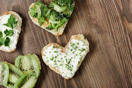 Photo pour Vue de dessus de la canape en forme de coeur avec fromage crémeux, brocoli, microvert, persil et kiwi sur la surface en bois - image libre de droit