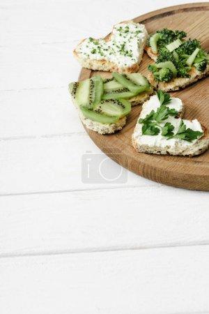 Canape en forme de coeur avec fromage crémeux, brocoli, microvert, persil et kiwi à bord sur une surface en bois blanc