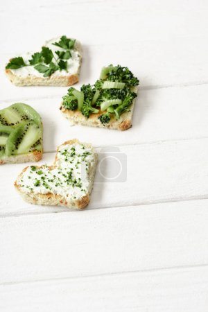 heart shaped canape with creamy cheese, broccoli, microgreen, parsley and kiwi on white wooden surface