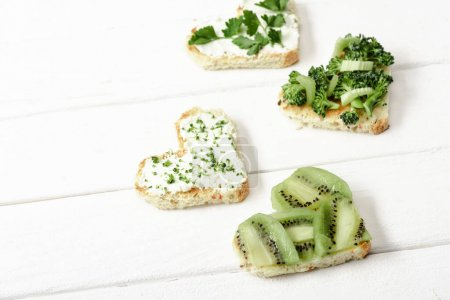 Photo for Heart shaped canape with creamy cheese, broccoli, microgreen, parsley and kiwi on white wooden surface - Royalty Free Image