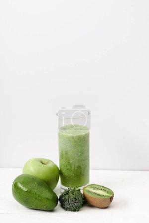Photo pour Smoothie vert en verre près de kiwi, brocoli, avocat et pomme sur surface en bois blanc - image libre de droit