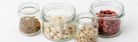 goji berries and sprouts in glass jars on white wooden surface, panoramic orientation