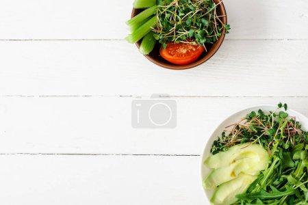 Photo pour Vue de dessus des légumes frais avec avocat et microvert dans des bols sur la surface en bois blanc - image libre de droit