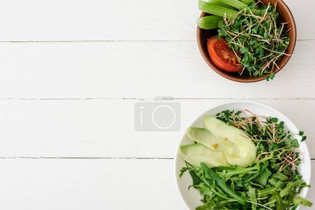 Photo for Top view of fresh vegetables with avocado and microgreen in bowls on white wooden surface - Royalty Free Image