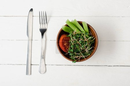 top view of tomato, celery and microgreen in bowl on white wooden surface with cutlery