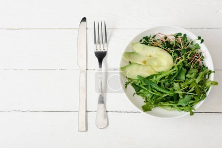 Photo for Top view of arugula, avocado and microgreen in bowl on white wooden surface with fork and knife - Royalty Free Image