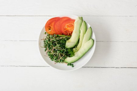 Photo for Top view of tomato, avocado and microgreen in bowl on white wooden surface - Royalty Free Image