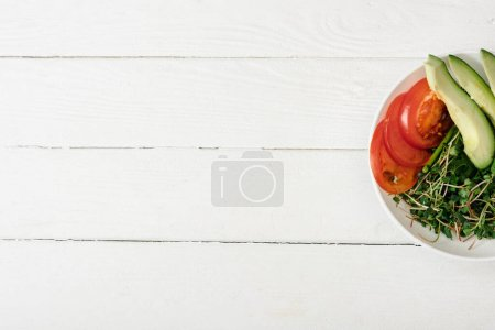 top view of tomato, avocado and microgreen in bowl on white wooden surface
