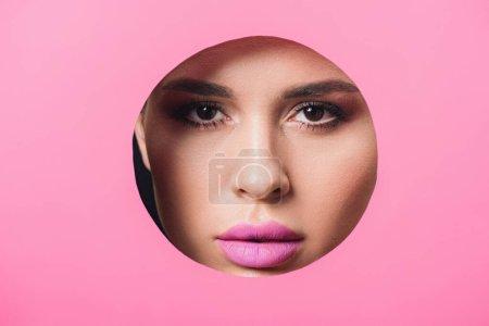 Photo pour Femme aux yeux fumés et aux lèvres roses regardant la caméra à travers un trou dans du papier - image libre de droit