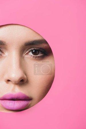 Photo pour Belle femme avec des yeux fumés et des lèvres roses regardant la caméra à travers le trou dans le papier - image libre de droit
