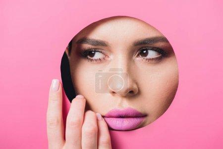 Photo pour Femme avec les yeux fumés et les lèvres roses regardant loin à travers le trou et touchant papier - image libre de droit