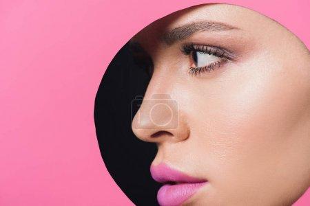 Photo pour Visage féminin avec lèvres roses dans un trou rond en papier sur fond noir - image libre de droit