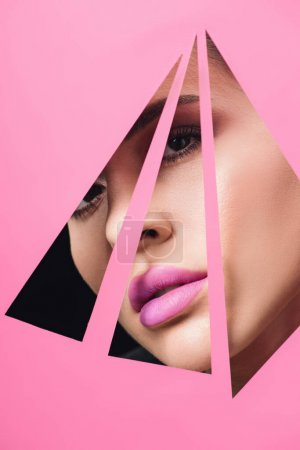 Photo for Beautiful woman with smoky eyes and pink lips looking across triangular holes in paper on black - Royalty Free Image