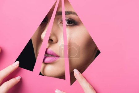 Photo for Beautiful woman with smoky eyes and pink lips looking at camera across triangular holes and touching paper on black - Royalty Free Image