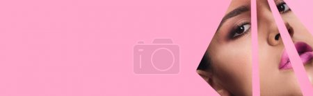 Photo for Beautiful woman with smoky eyes and pink lips looking at camera across triangular holes in paper, panoramic shot - Royalty Free Image