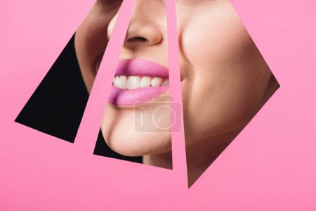 Photo for Cropped view of woman with pink lips smiling across triangular holes in paper on black background - Royalty Free Image
