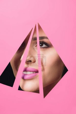 Photo for Woman with smoky eyes and pink lips smiling across triangular holes in paper on black background - Royalty Free Image