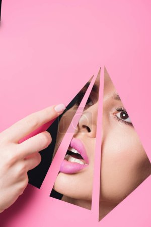 Photo for Woman with open mouth and pink lips looking across triangular holes and touching paper with hand on black background - Royalty Free Image