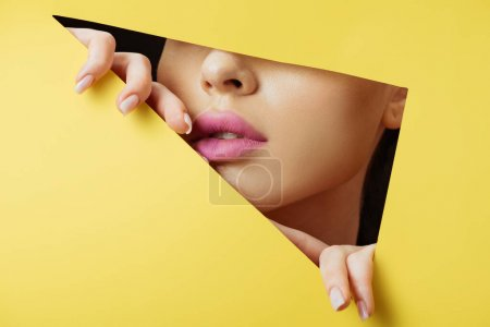 Photo for Cropped view of woman with pink lips touching yellow paper across triangular hole on black background - Royalty Free Image
