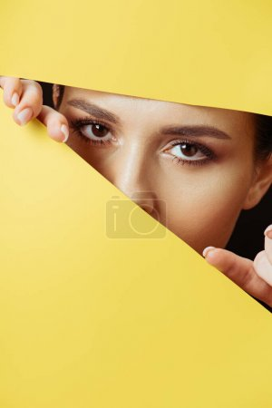 Photo for Woman looking at camera across hole and touching yellow paper with fingers - Royalty Free Image