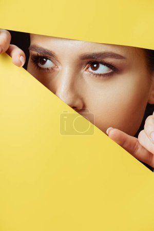 Photo for Woman looking away across hole and touching yellow paper with fingers - Royalty Free Image