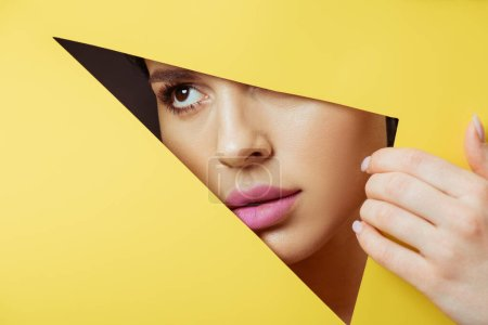 Photo for Woman with pink lips in triangular hole touching yellow paper with hand - Royalty Free Image