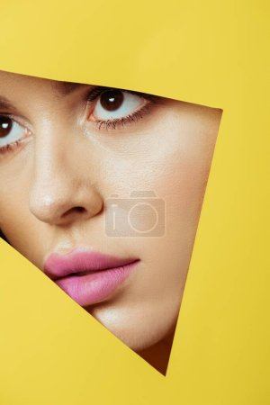 Photo for Woman with pink lips looking across triangular hole in yellow paper - Royalty Free Image