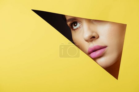 Woman with pink lips looking across triangular hole in yellow paper on black background