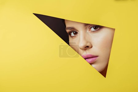 Photo for Woman with pink lips looking at camera across triangular hole in yellow paper on black - Royalty Free Image