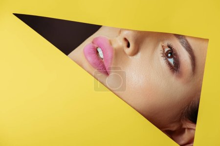 Photo for Girl with pink lips looking across triangular hole in yellow paper on black - Royalty Free Image