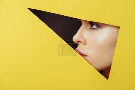 Foto de Perfil femenino en agujero triangular en papel amarillo sobre fondo negro - Imagen libre de derechos