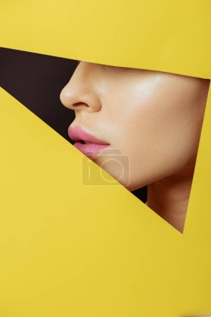 Photo for Cropped view of female face with pink lips in triangular hole in yellow paper on black - Royalty Free Image