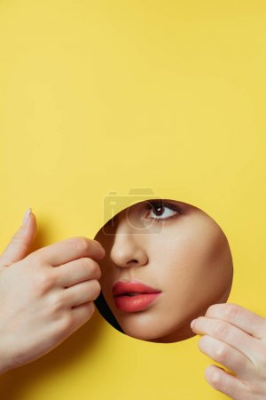 Woman with coral lips looking across round hole and touching yellow paper with hands