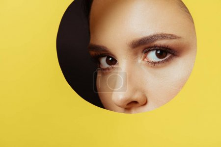 Photo for Girl with smoky eyes looking at camera across hole in yellow paper on black background - Royalty Free Image