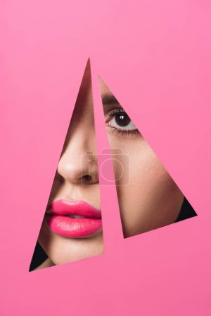 Photo for Female face with pink lips across triangular holes in paper - Royalty Free Image