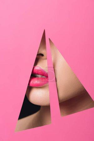 Photo pour Vue recadrée du visage féminin avec des lèvres roses dans des trous triangulaires en papier sur noir - image libre de droit