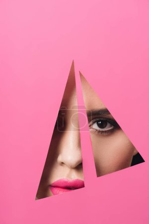 Photo for Girl with smoky eyes and pink lips looking at camera across triangular holes in paper - Royalty Free Image