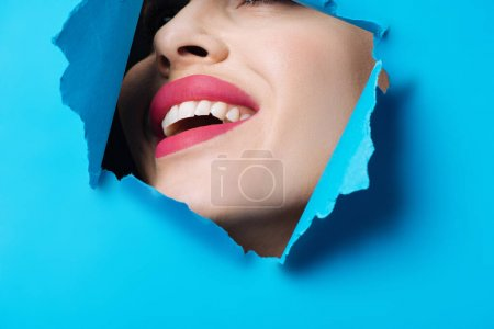 Photo for Happy woman with pink lips smiling across ripped blue paper - Royalty Free Image