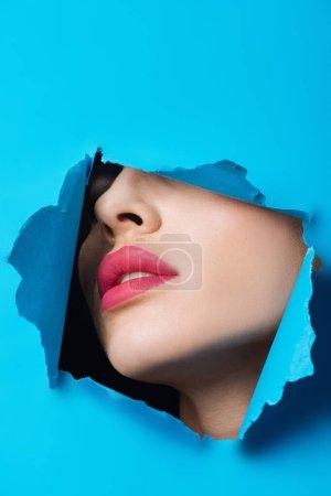 Foto de Cara femenina con labios rosados en agujero en papel azul brillante. - Imagen libre de derechos