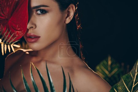 Photo for Selective focus of sexy woman near leaves covering face with red anthurium and looking at camera isolated on black - Royalty Free Image
