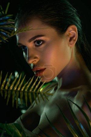 Photo pour Portrait de femme avec des feuilles autour isolé sur noir - image libre de droit